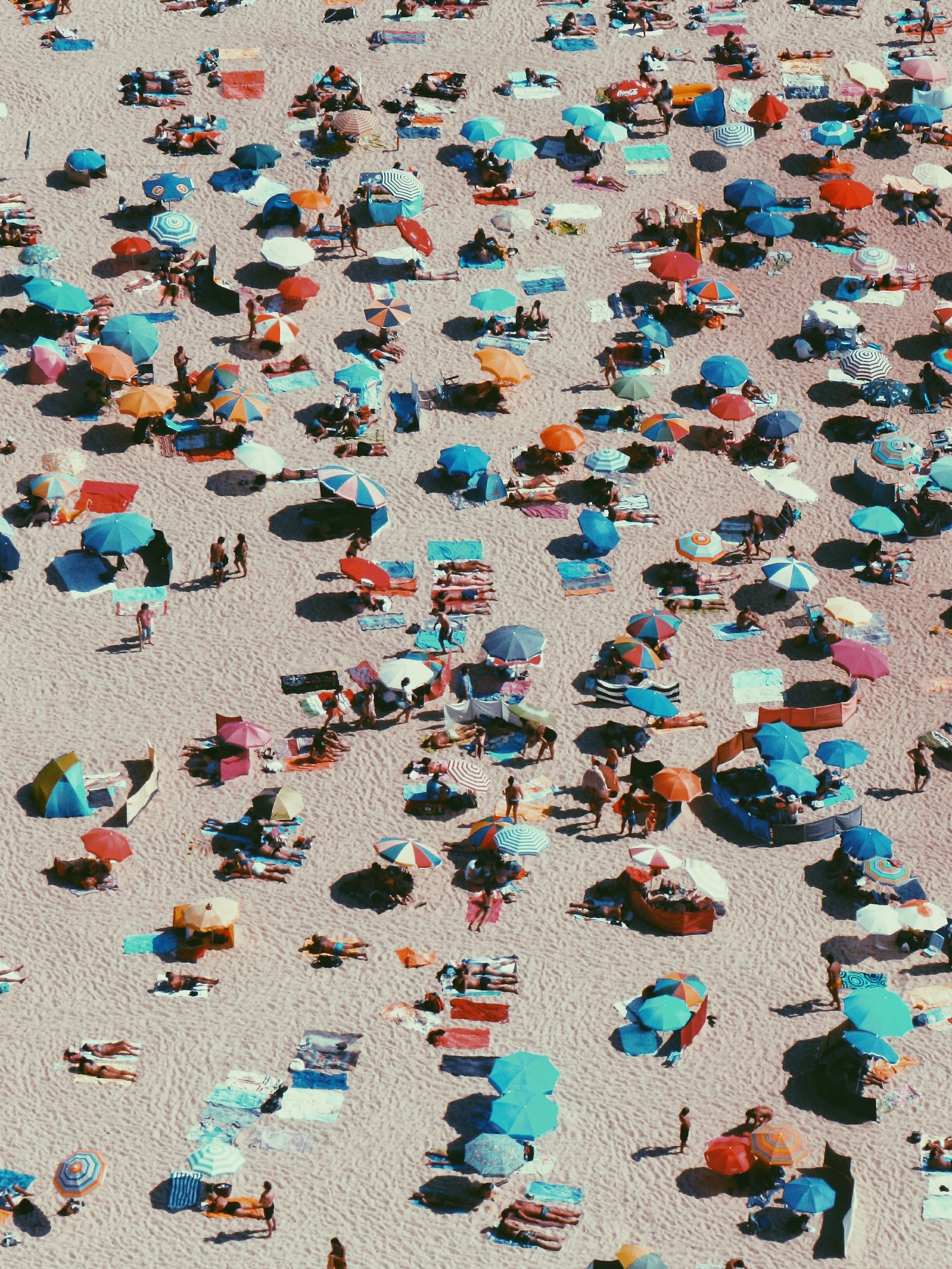 aerial photography of people and parasols on beach shoreline at daytime