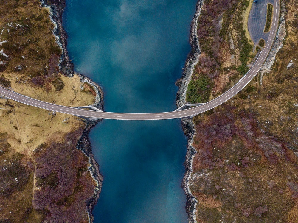 high angle photography of concrete road connecting two lands