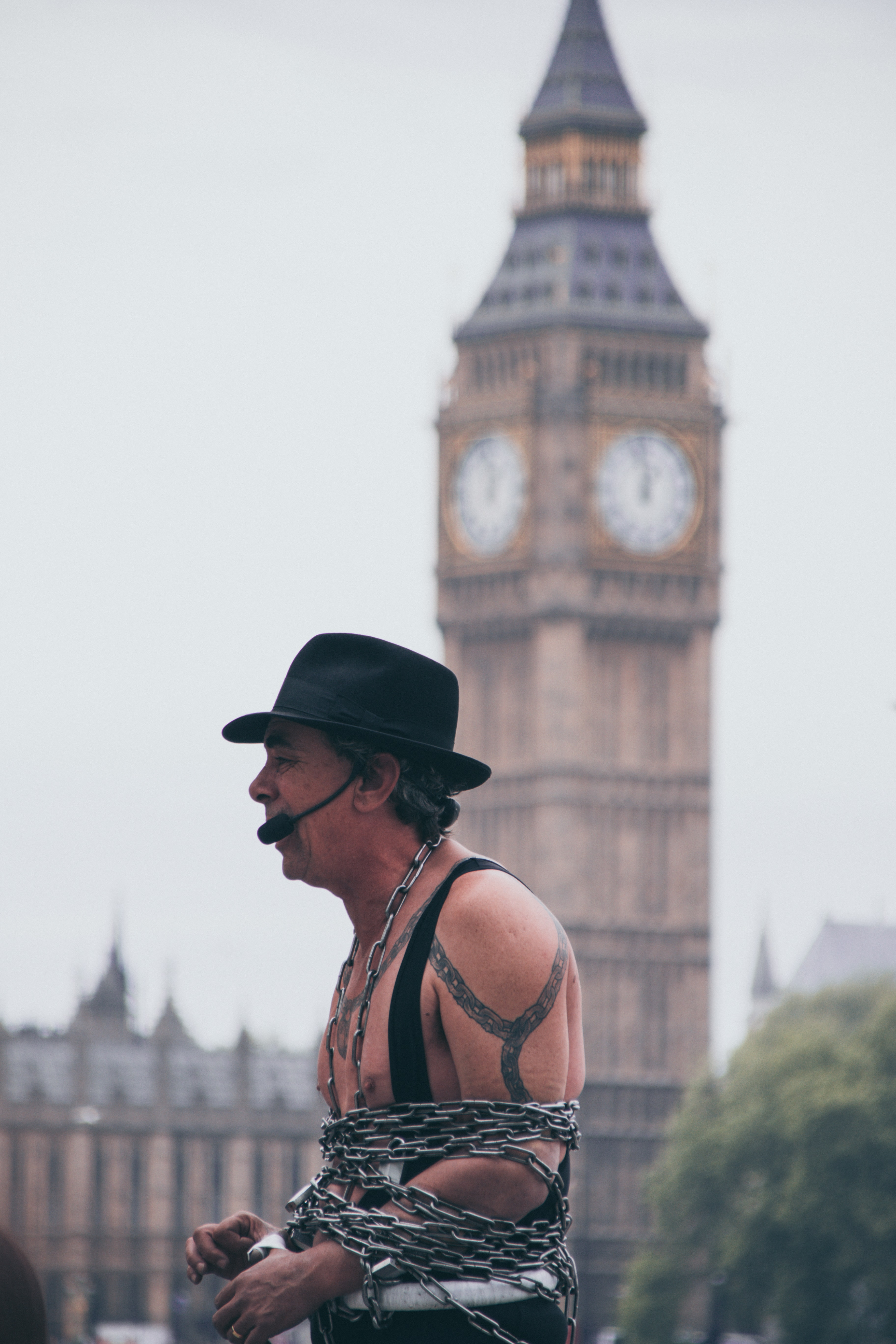 selective focus photo of man covered with chain with microphone with a view of big ben