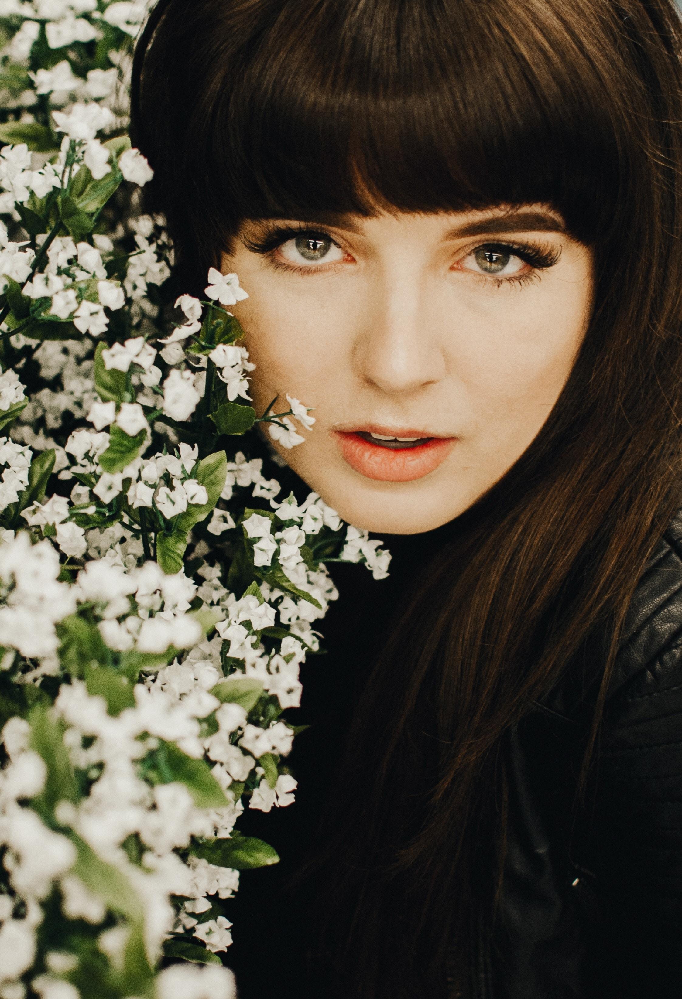 woman taking selfie near white flowers