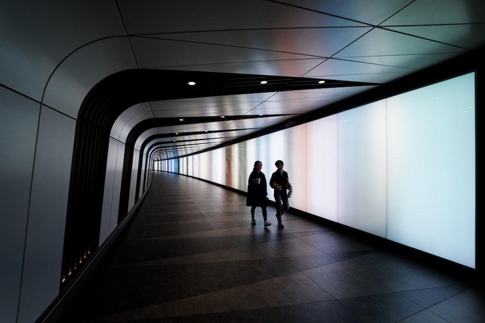 two people walking on hallway