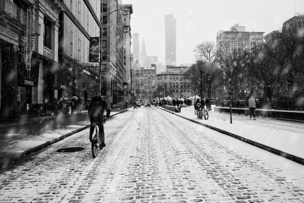 grayscale photo of man riding bicycle on road