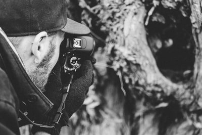 grayscale photo of man taking photo noir zoom background
