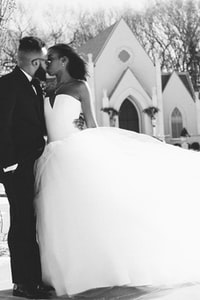 grayscale photography of kissing bride and groom near concrete church