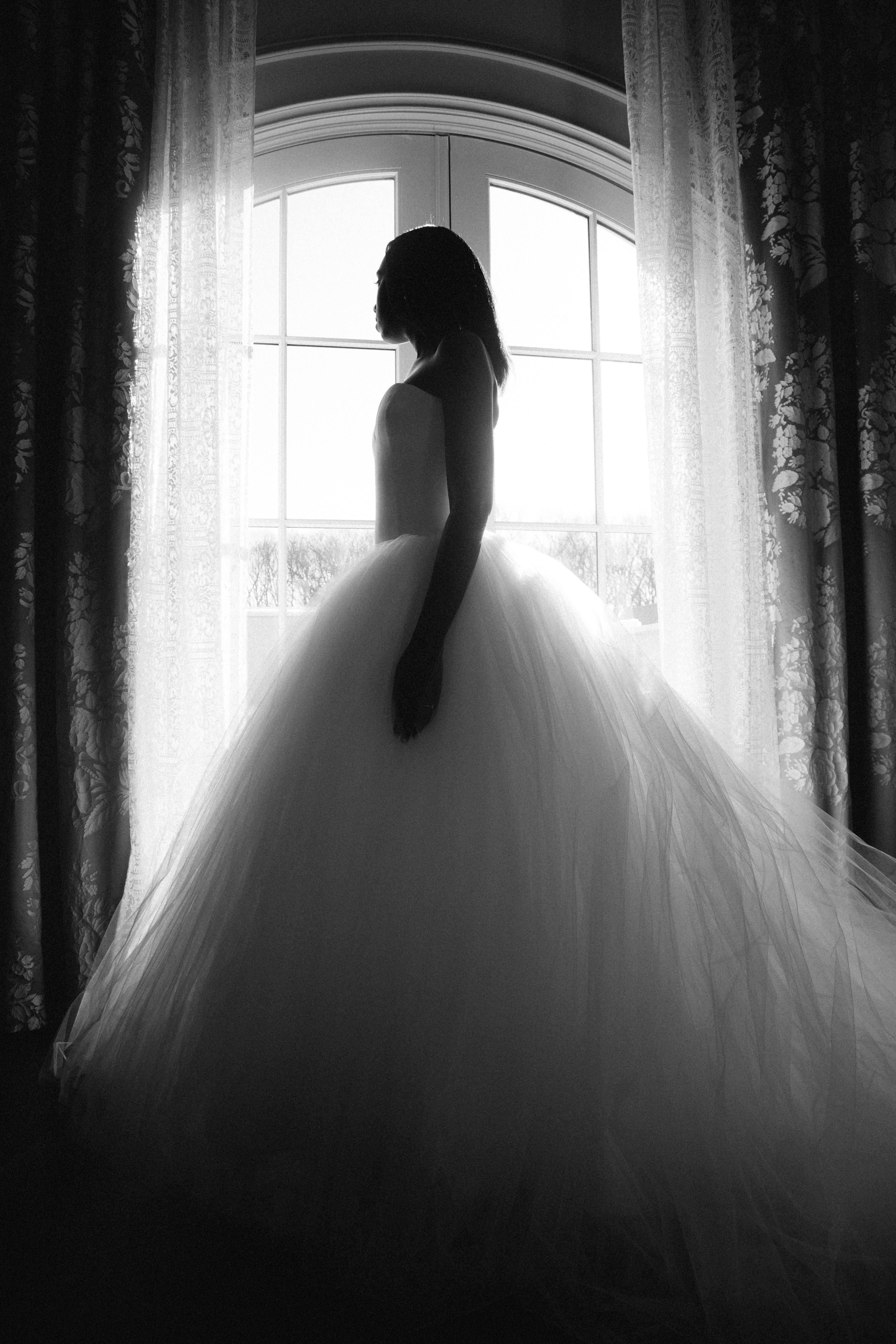 woman wearing wedding gown standing near window during daytime