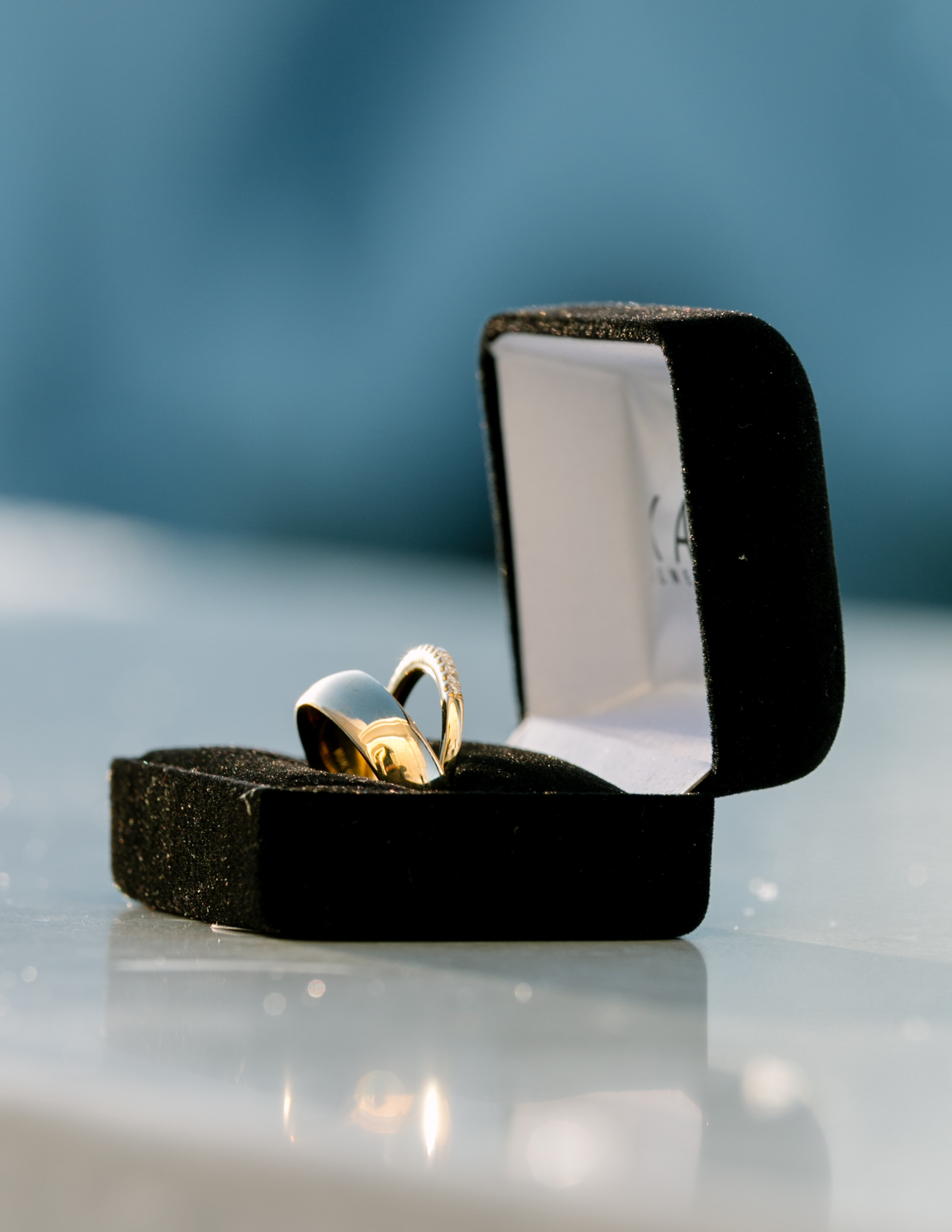 silver-colored bridal ring set on box on top of white surface