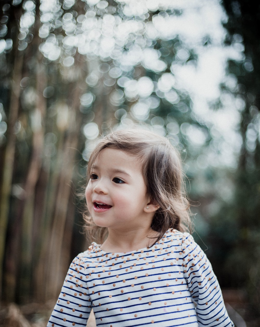 girl wearing white striped shirt near on tree forest