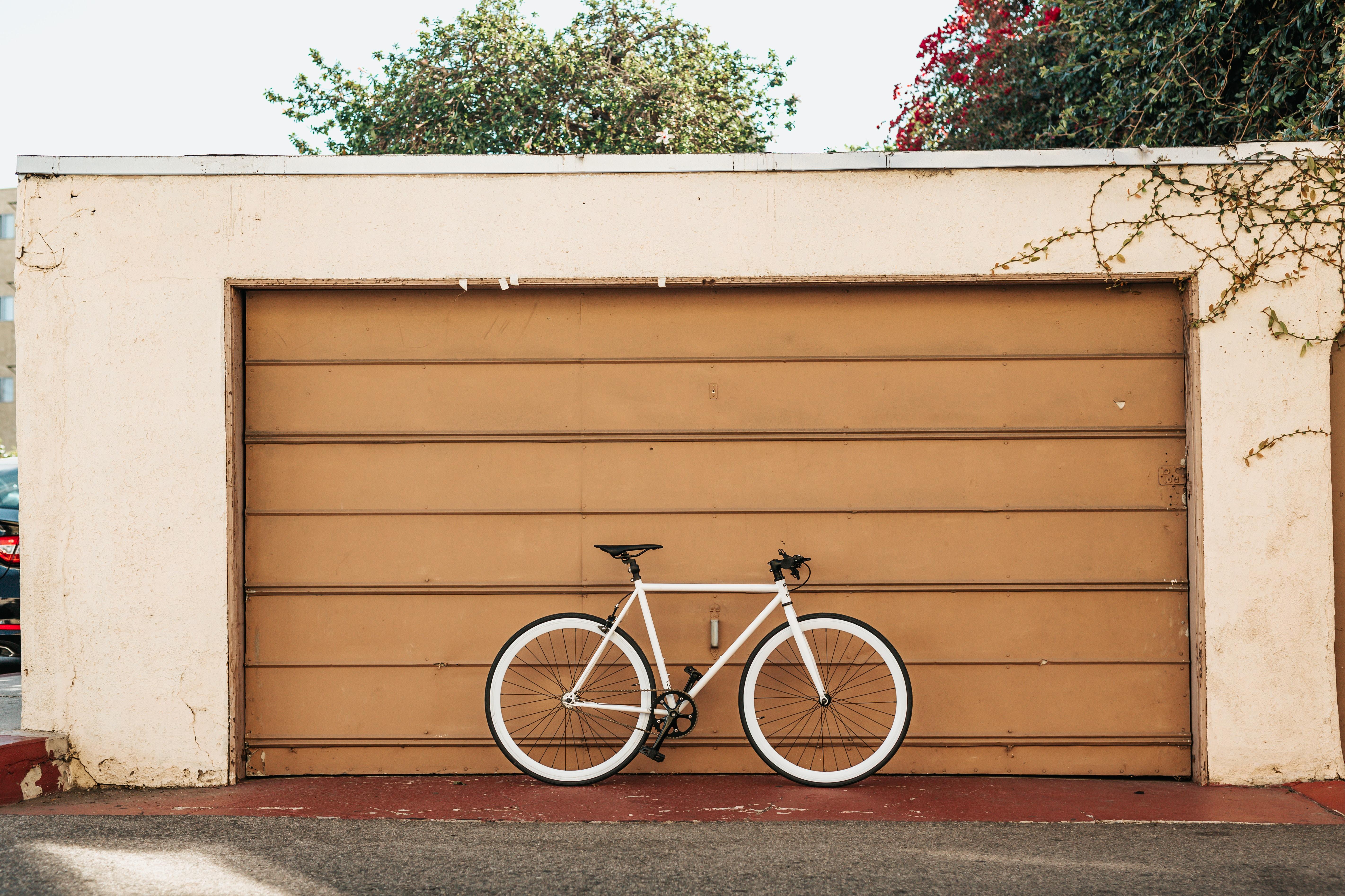white bike leaning on brown roller shutter