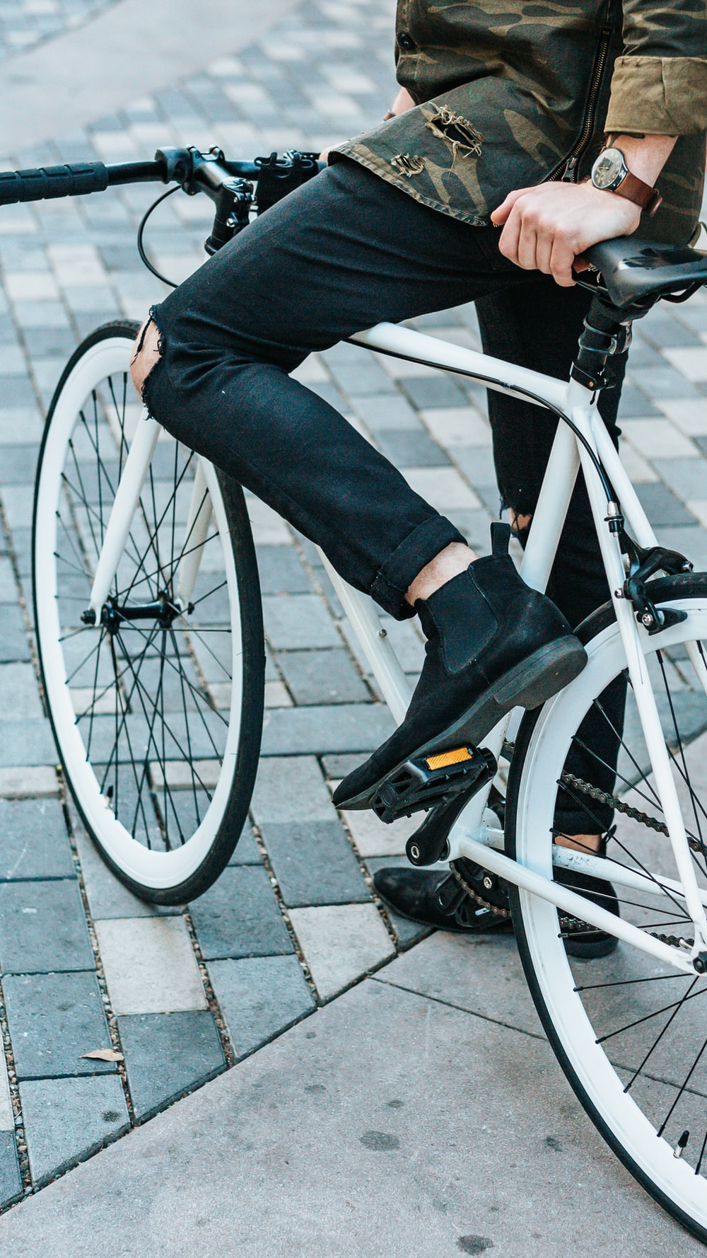 man wearing black pants riding white commuter bike