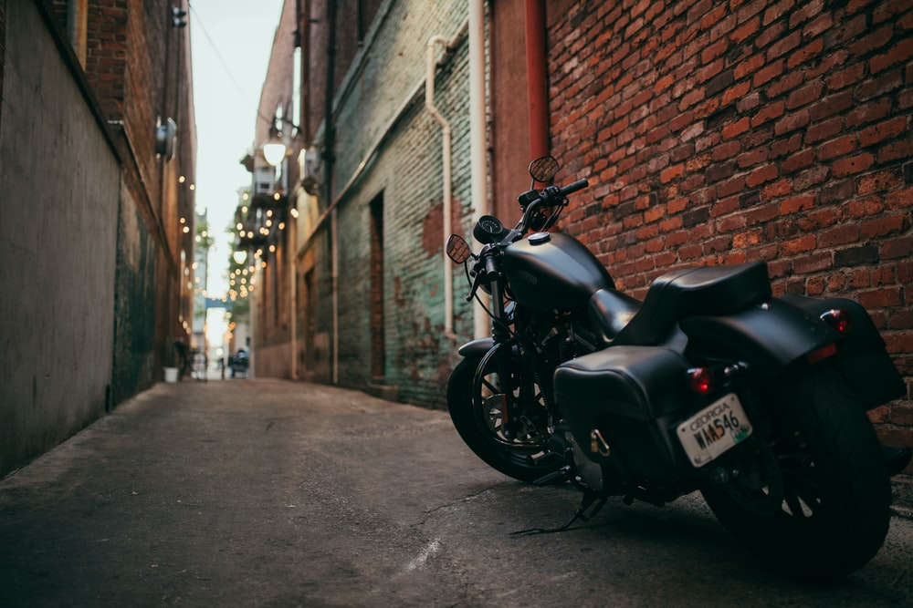 black cruiser motorcycle parked at the middle of the alley