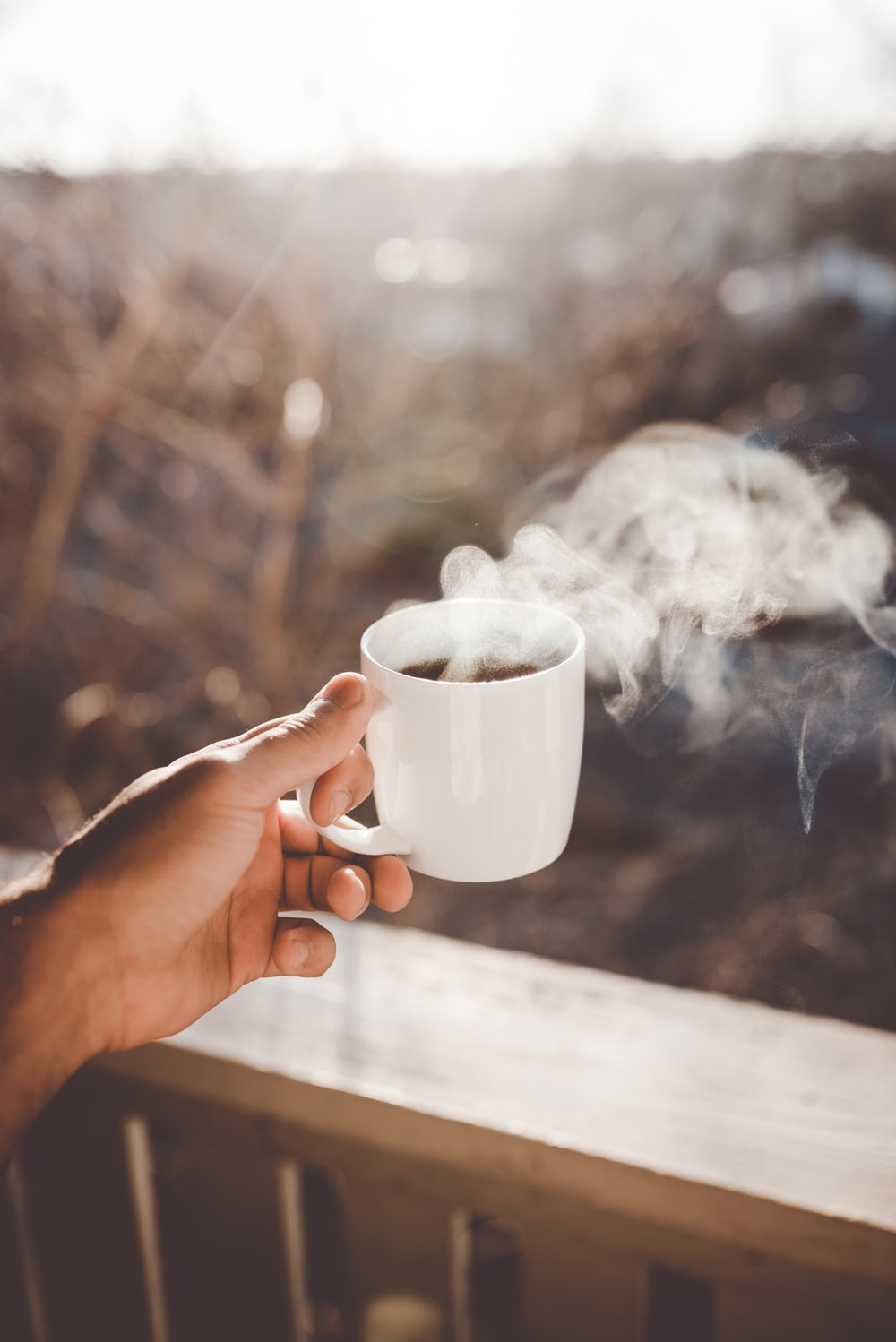 person holding white ceramic cup with hot coffee
