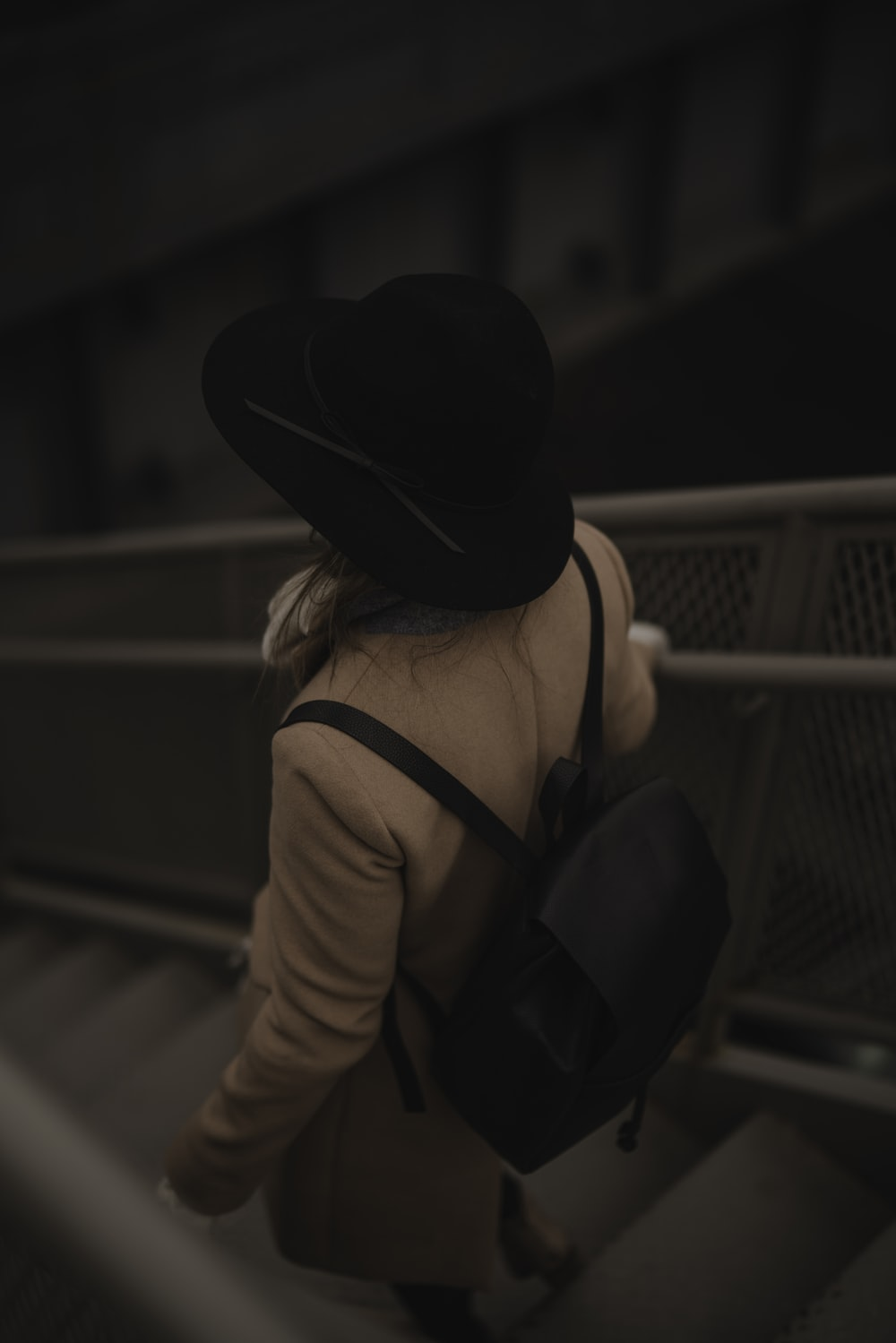person carrying black backpack while walking downards of stair