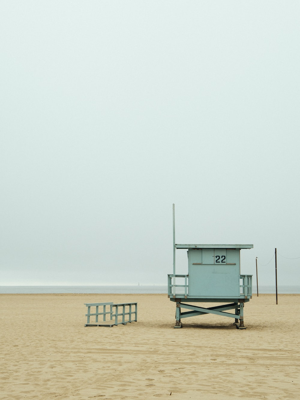 teal lifeguard shed near beach at daytime