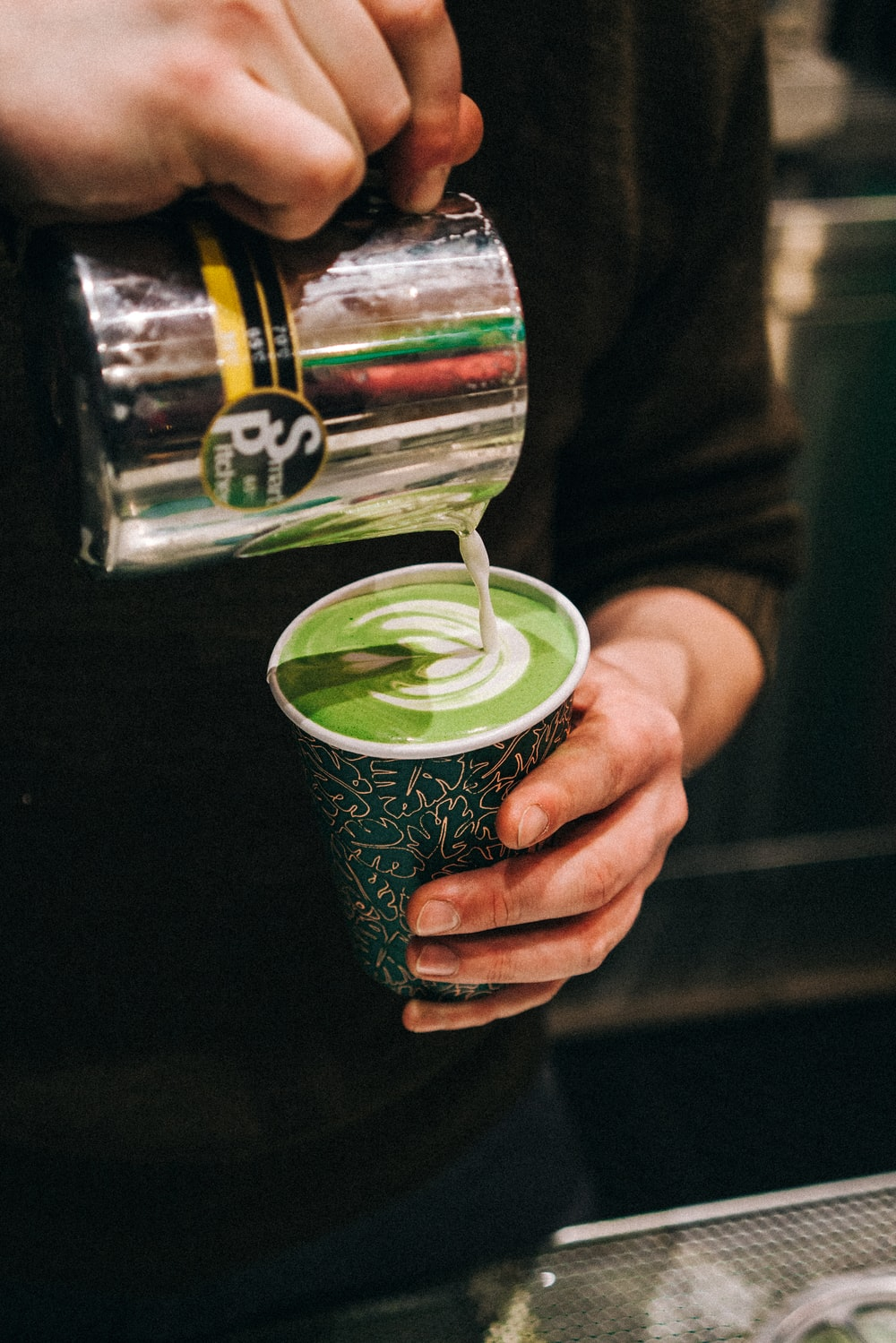 person holding green and white plastic cup and gray smart pitcher while pouring latte