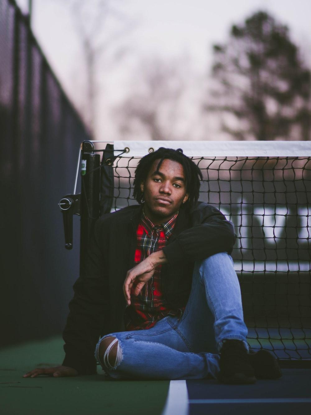 man sitting beside black net during daytime