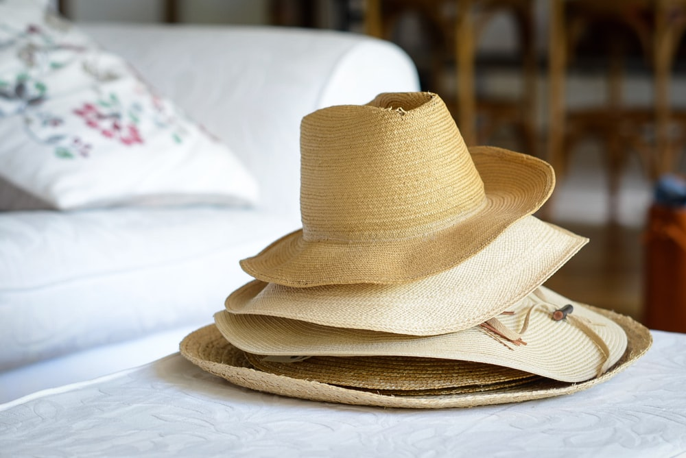 five brown straw nesting hats on white textile