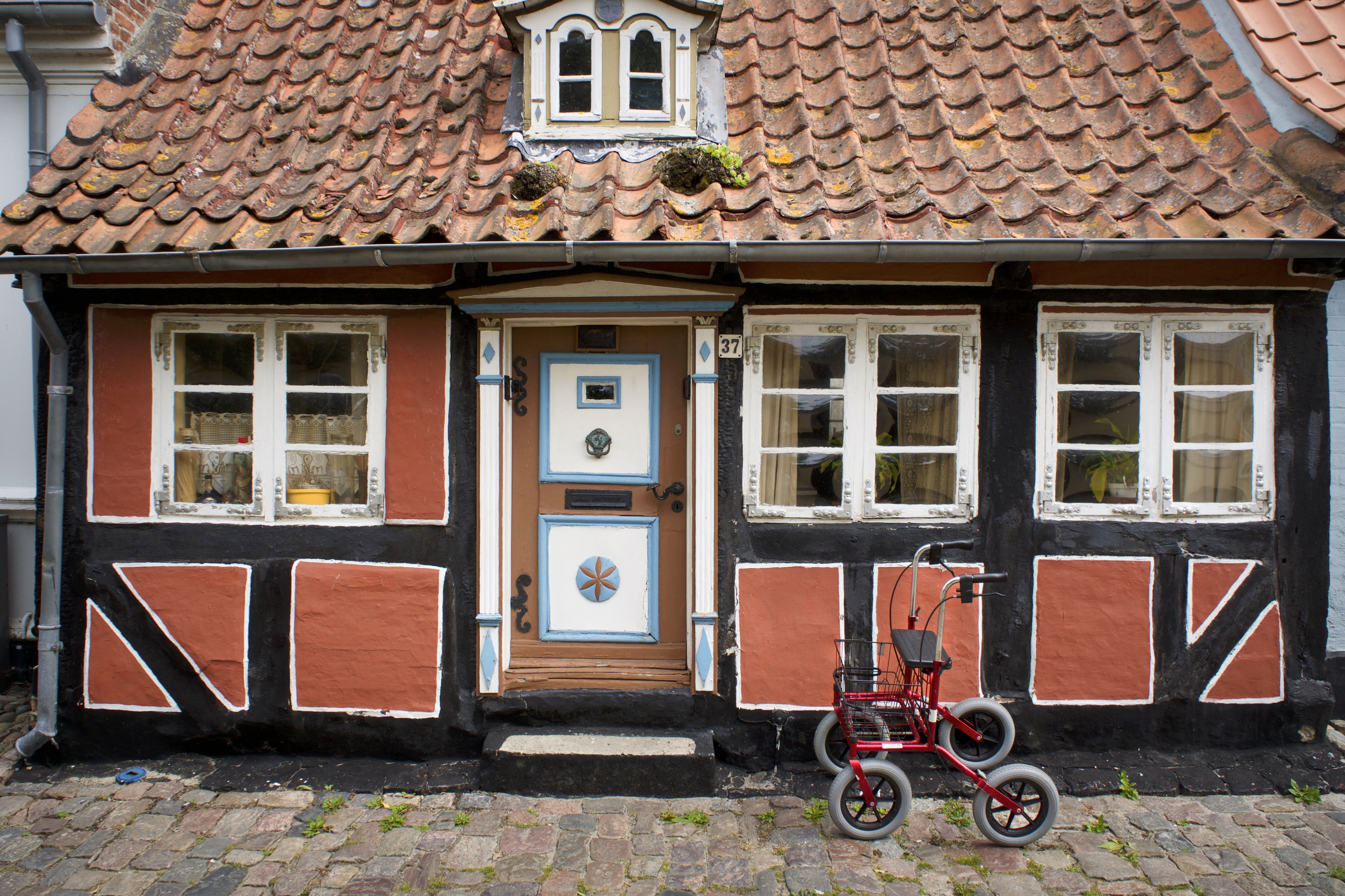 red rollator beside black concrete house during daytime
