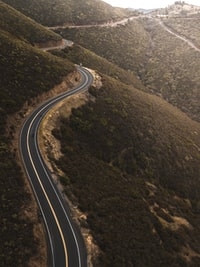 aerial photo of black concrete top road near green mountains