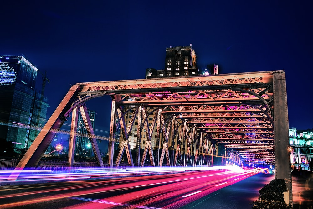 time lapse and light streaks photo of vehicle on bridge with high rise buildings in distant