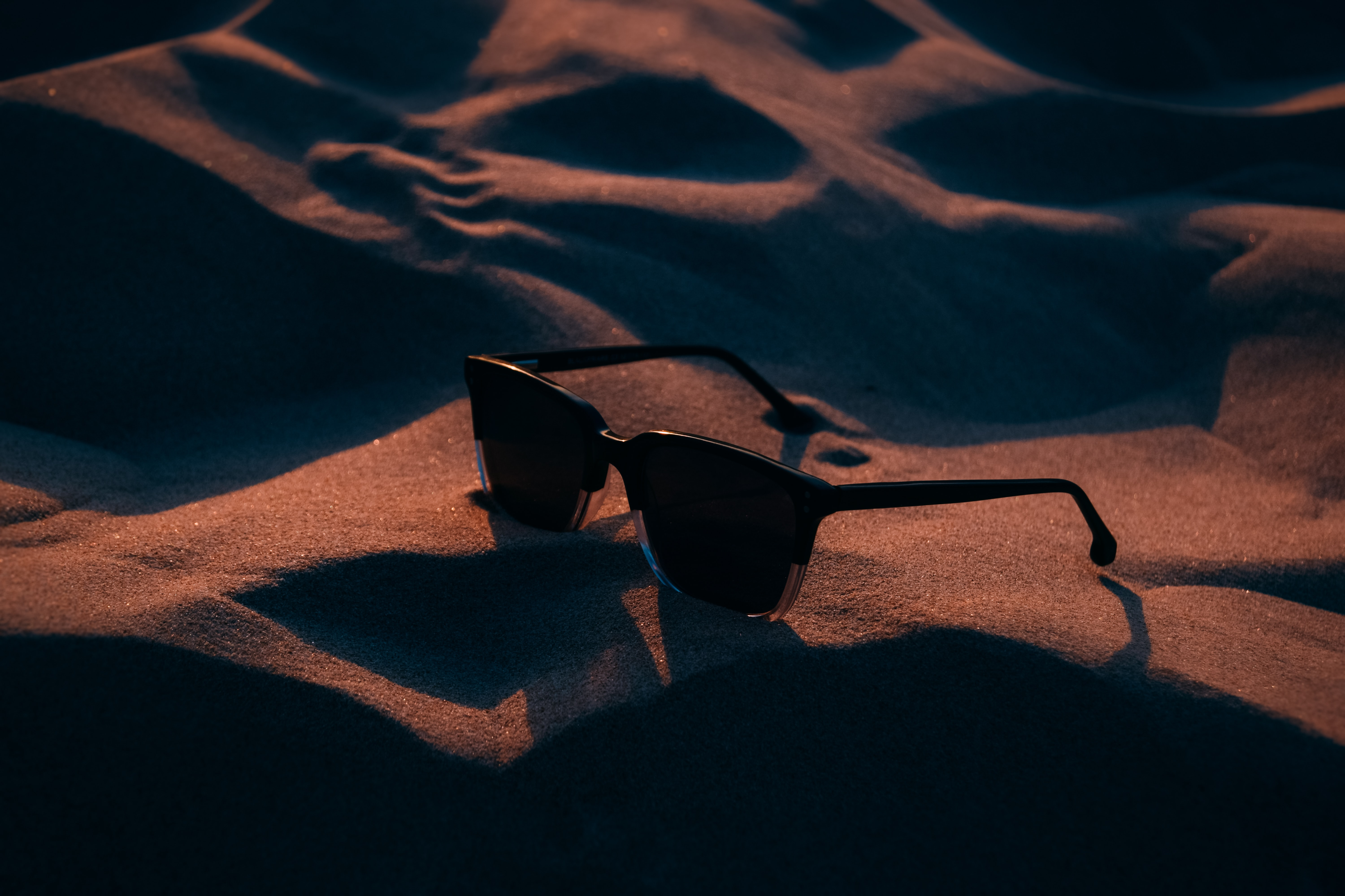 silhouette photography of black framed sunglasses on sand