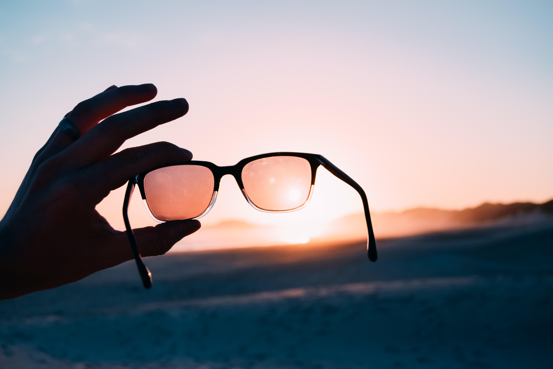 person holding Wayfarer-style sunglasses
