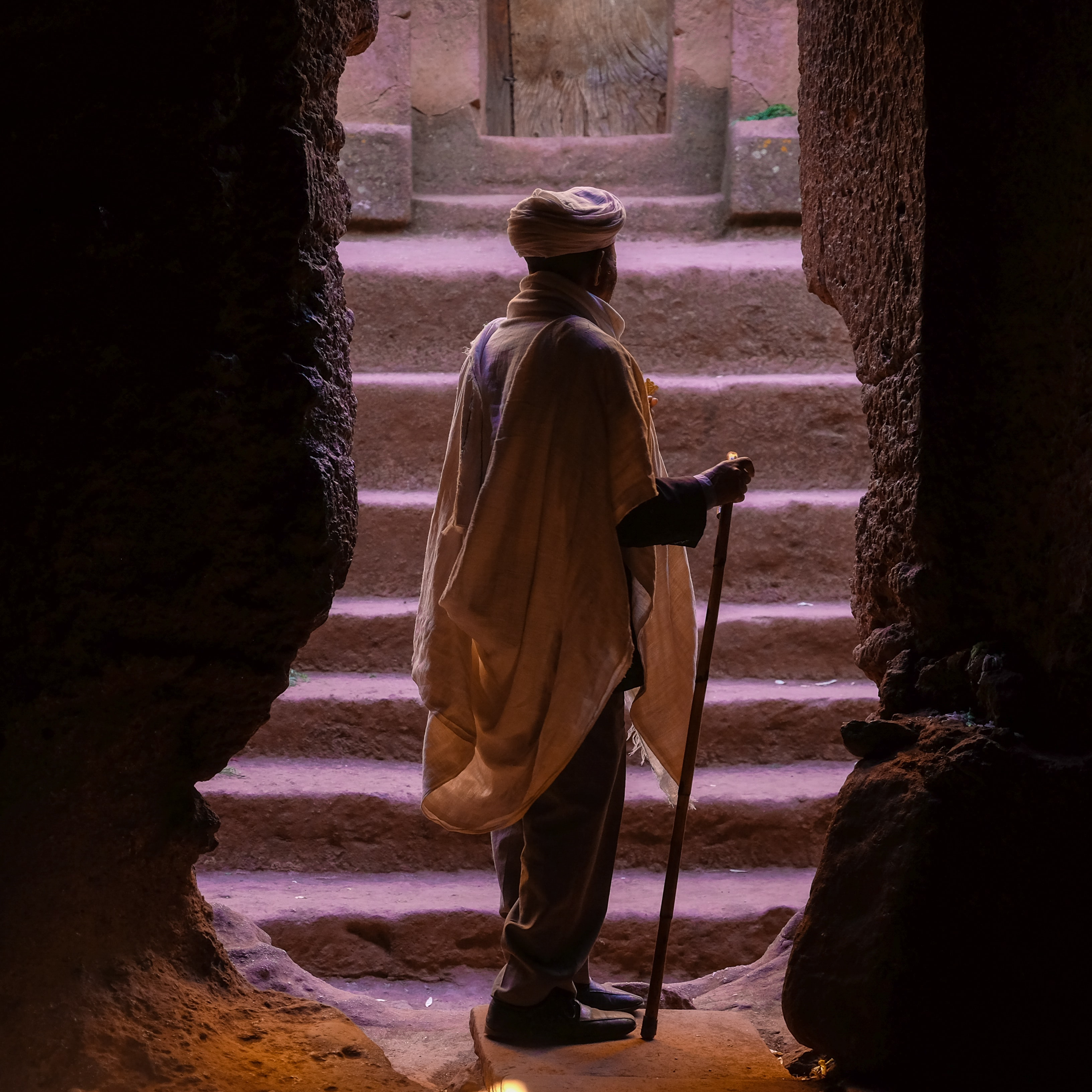 man standing on brown stone cave entrance while holding cane
