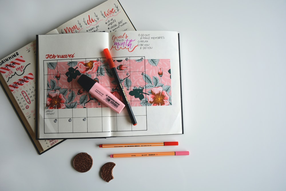 monthly planner with pink highlighter and pens