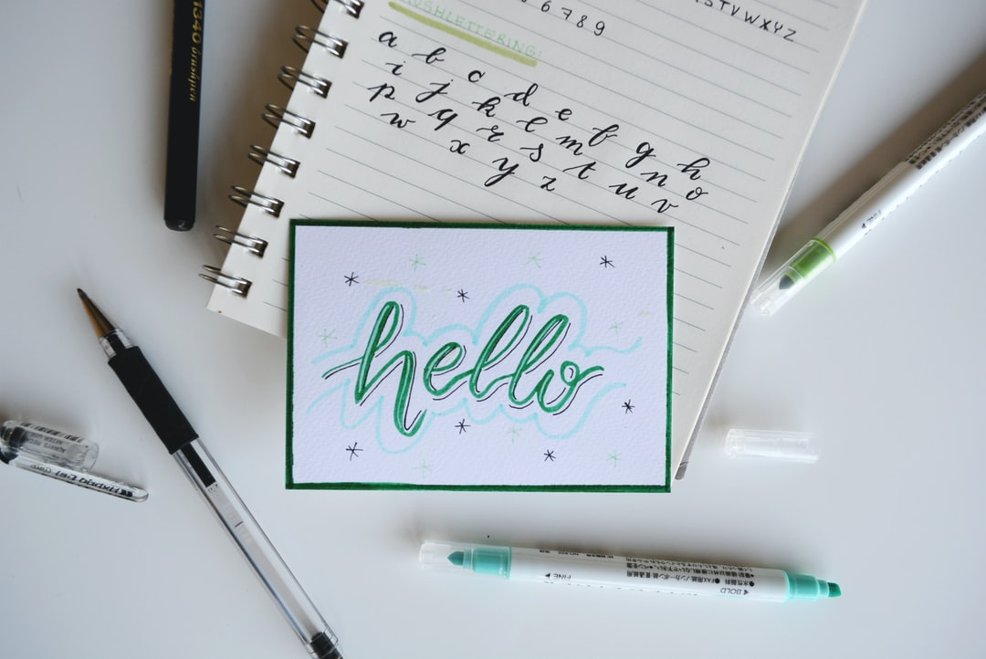 """Hello"" sketched onto a notecard on top of a notebook with handwritten characters."