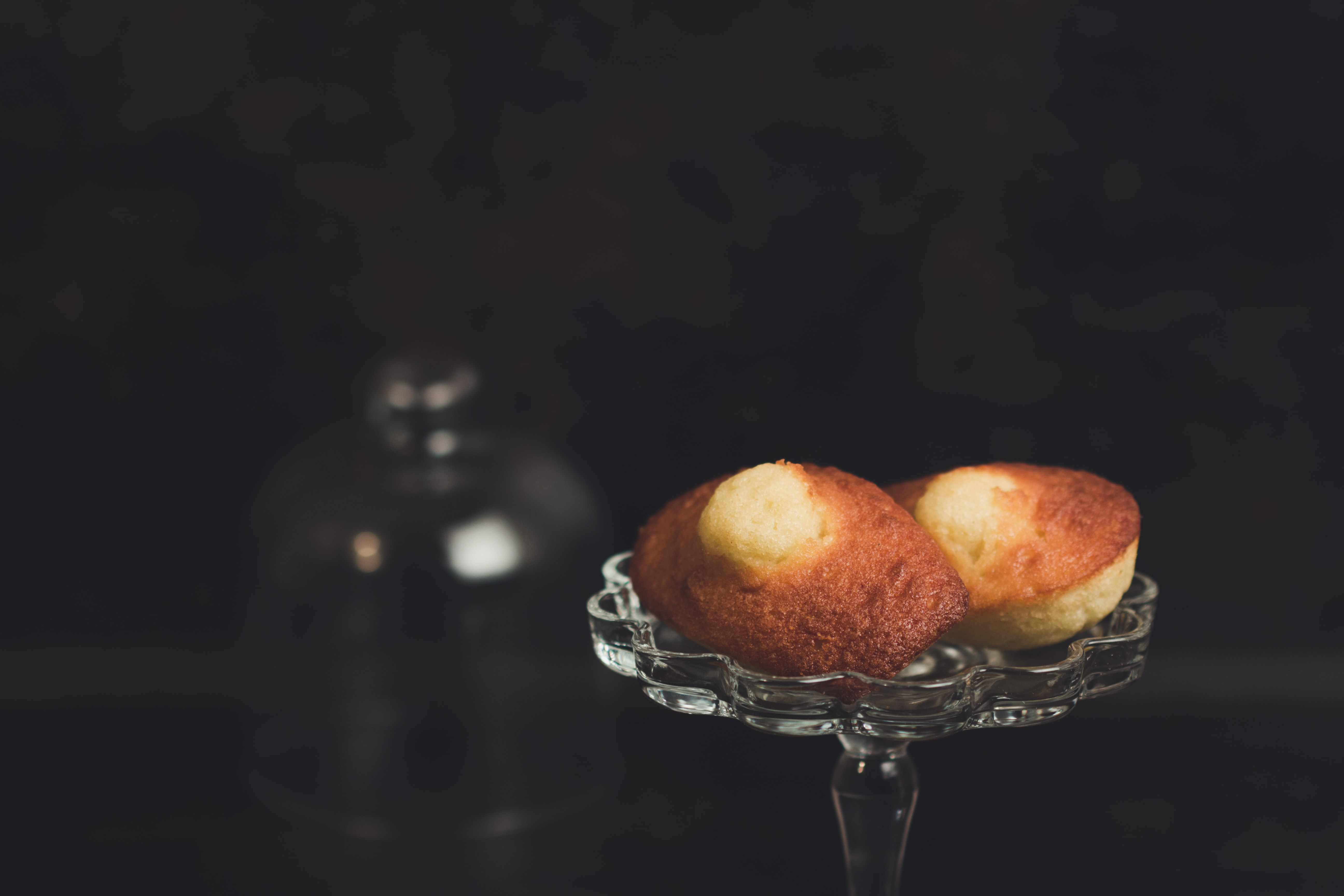 two baked breads placed on clear glass cupcake stand in focus photography