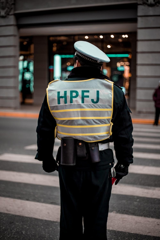 man wearing black and gray HPFJ suit standing on crosswalk closeup pho o