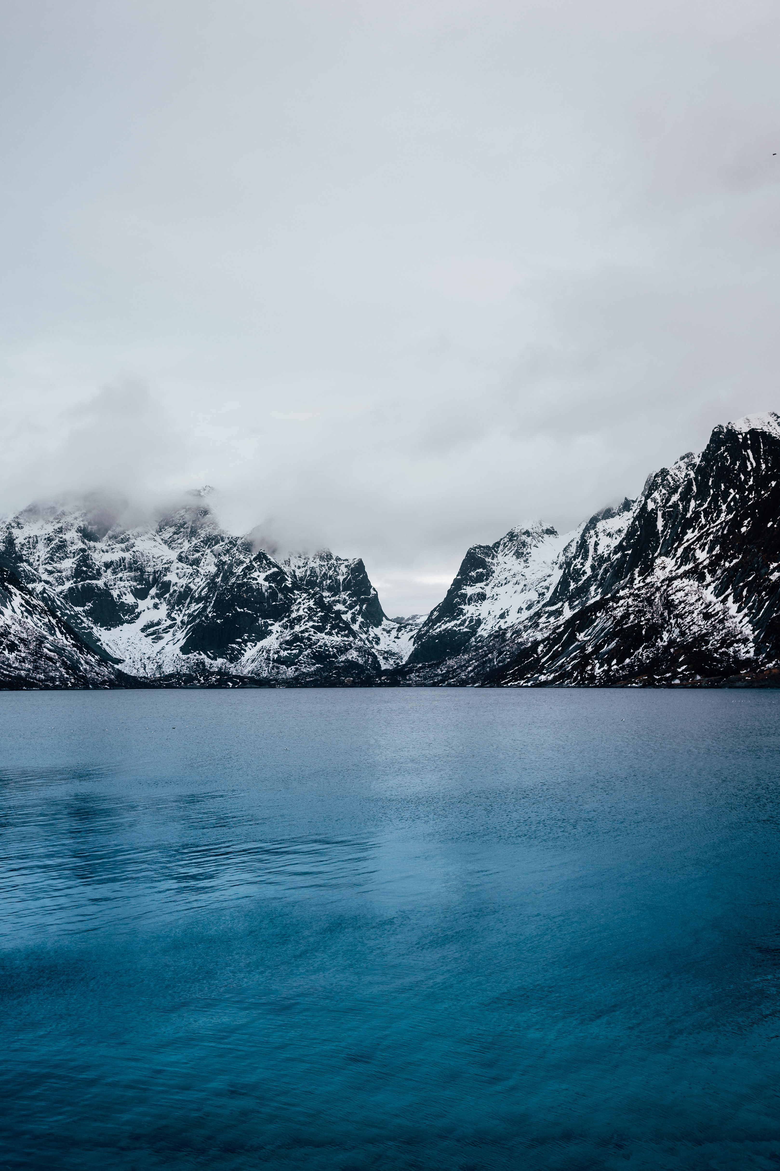 blue calm body of water and snow covered mountain under grey clouds at daytime