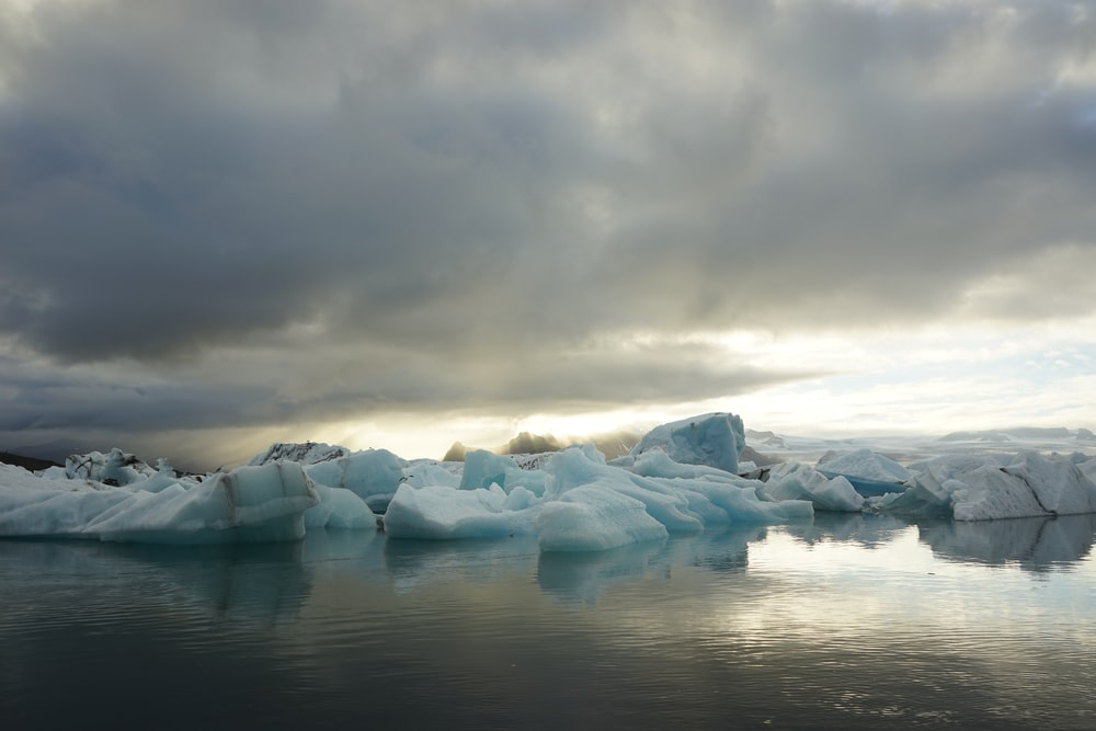glacier island and sea under cloudy sky during daytime