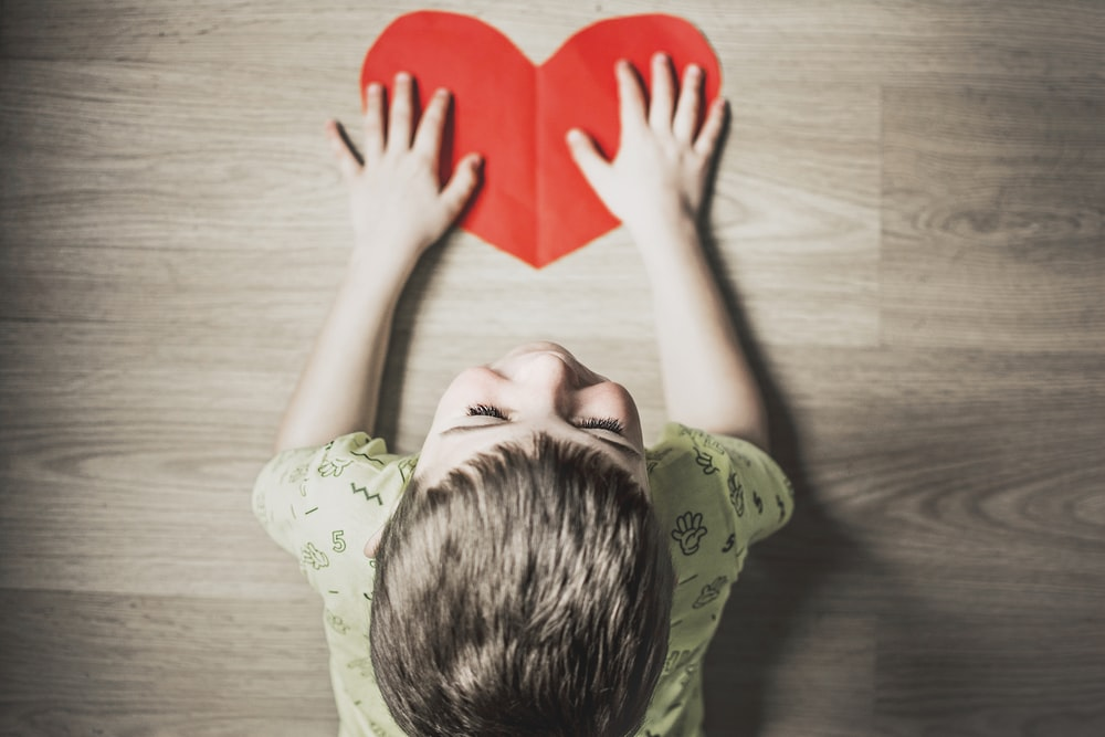 boy in green shirt holding red paper heart cutout on brown table