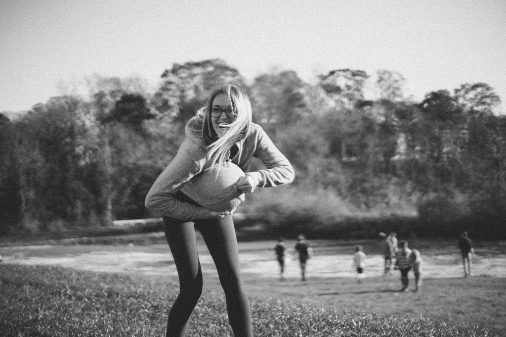 woman in gray jacket playing with ball
