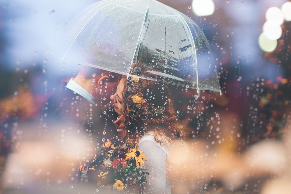 a bride and groom kiss in the rain under an umbrella