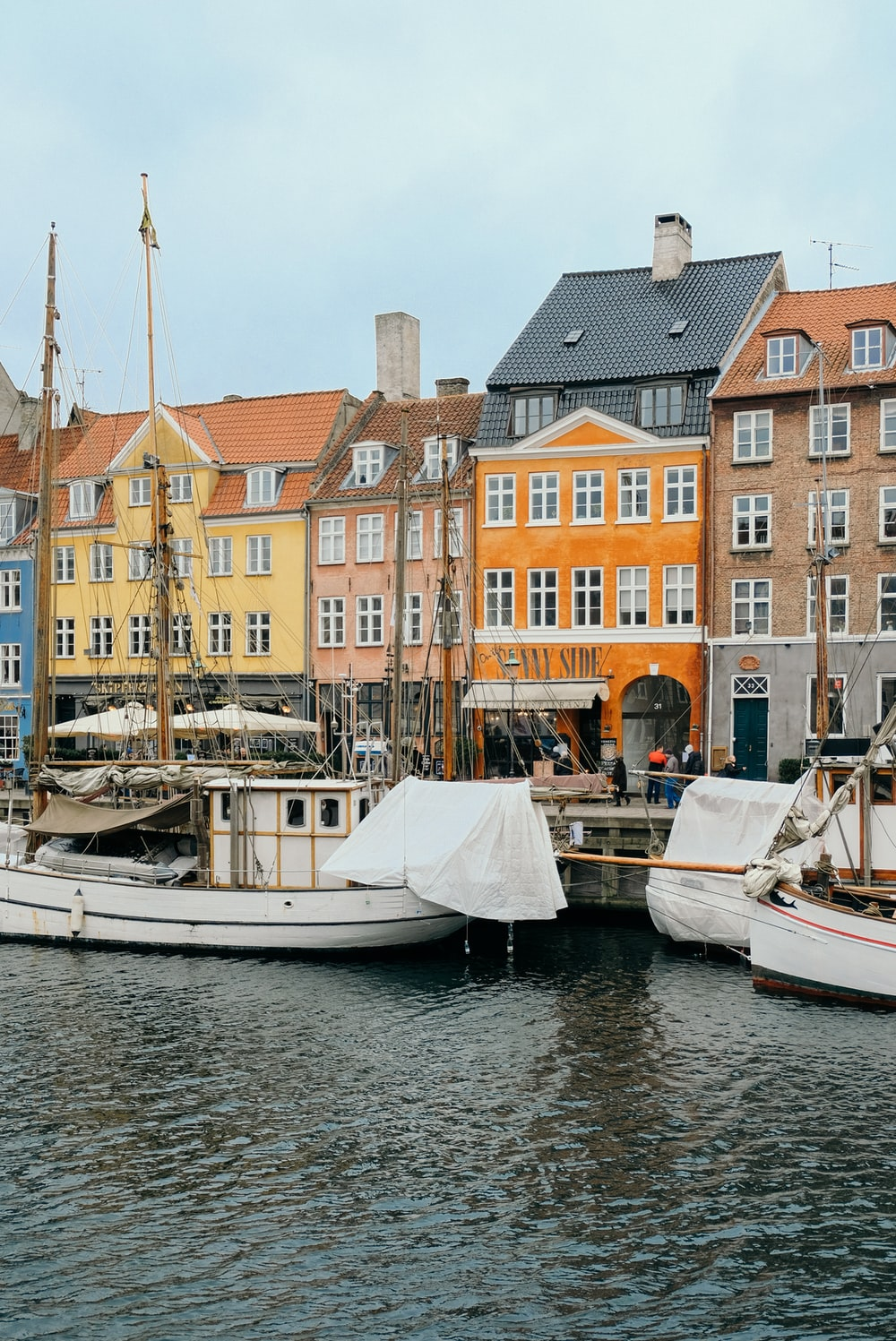 white wooden boats docks near assorted-color concrete houses during daytime