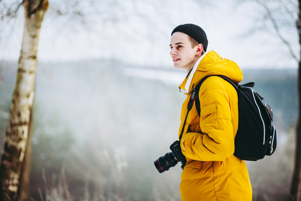 selective focus photography of man standing on cliff with DSLR camera hanging on neck