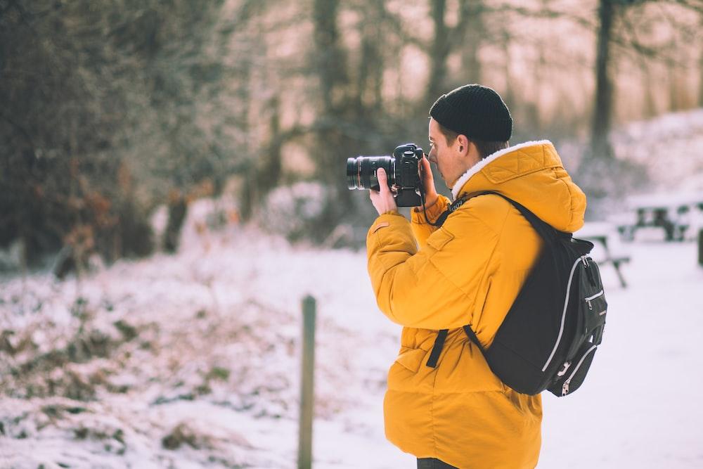 man wearing brown pull-over jacket using black camera