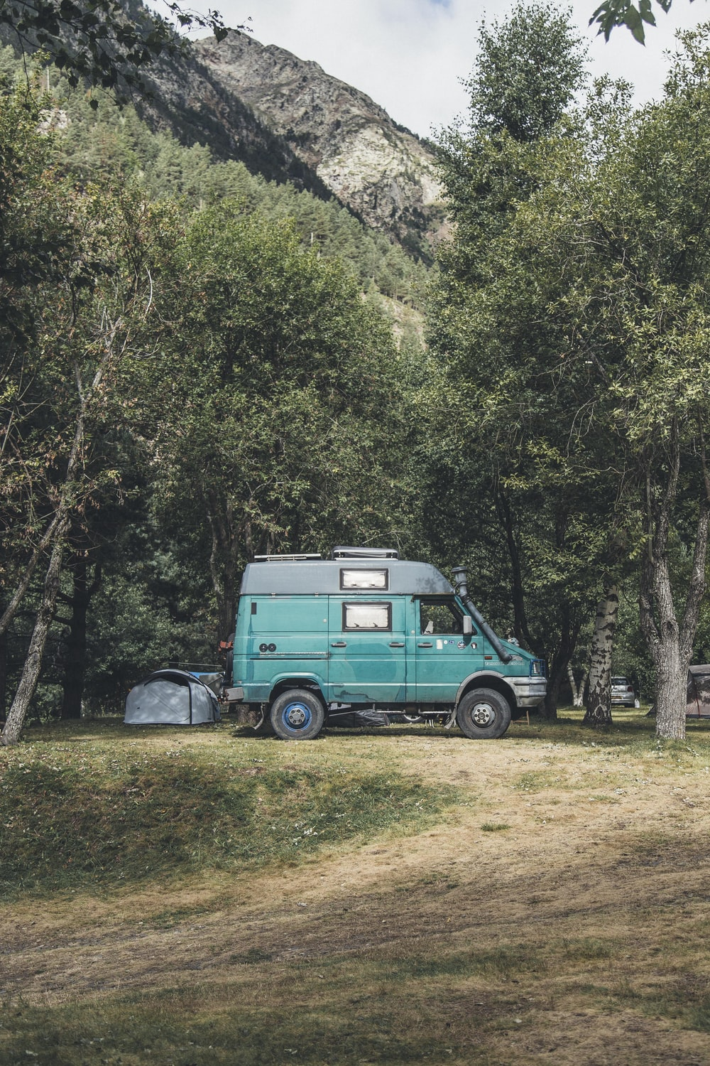 landscape photography of parked teal and black conversion van near trees