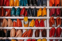 assorted-color shoe lot on white wooden shelf