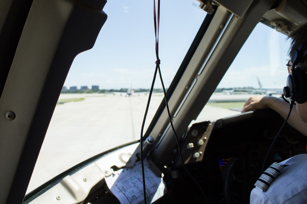 pilot wearing black headset inside aircraft with glass windshield