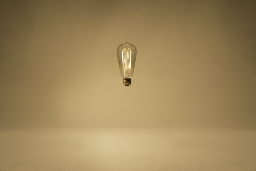 lighted clear light bulb floating in mid air