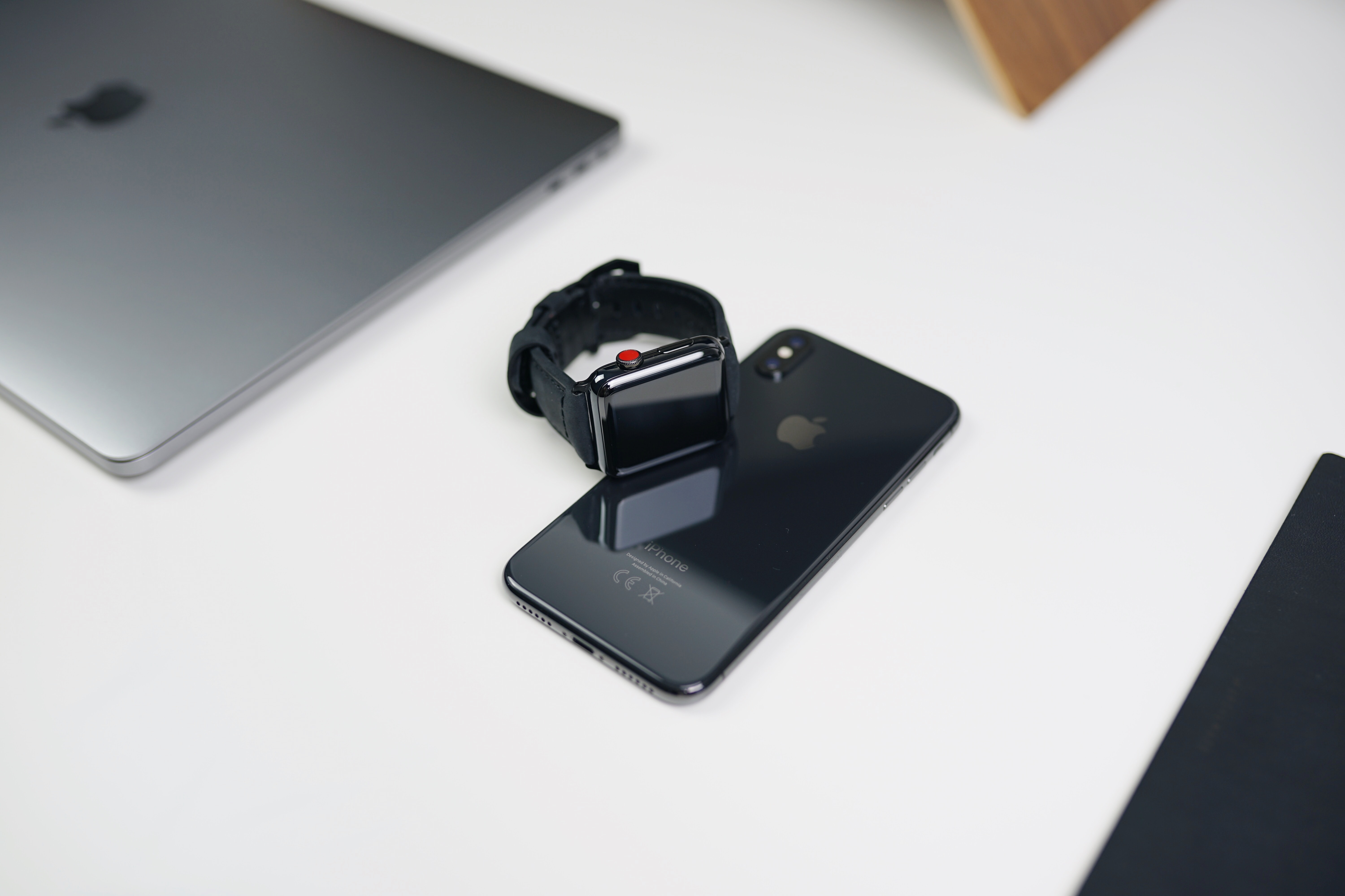 space gray aluminum case Apple Watch with black Sport Band on space gray iPhone X beside silver MacBook
