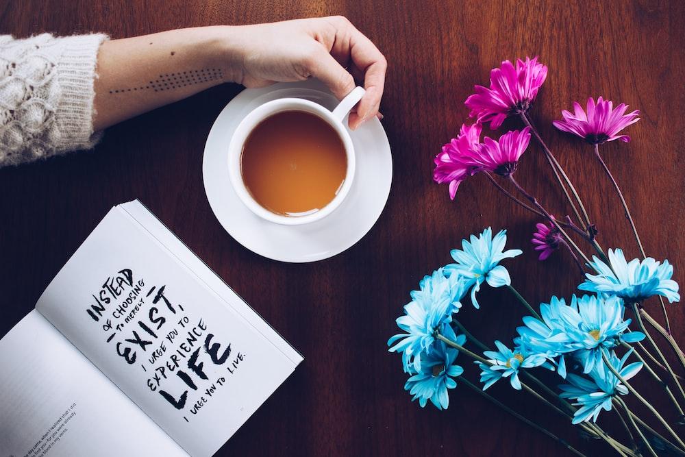 person holding mug beside flowers