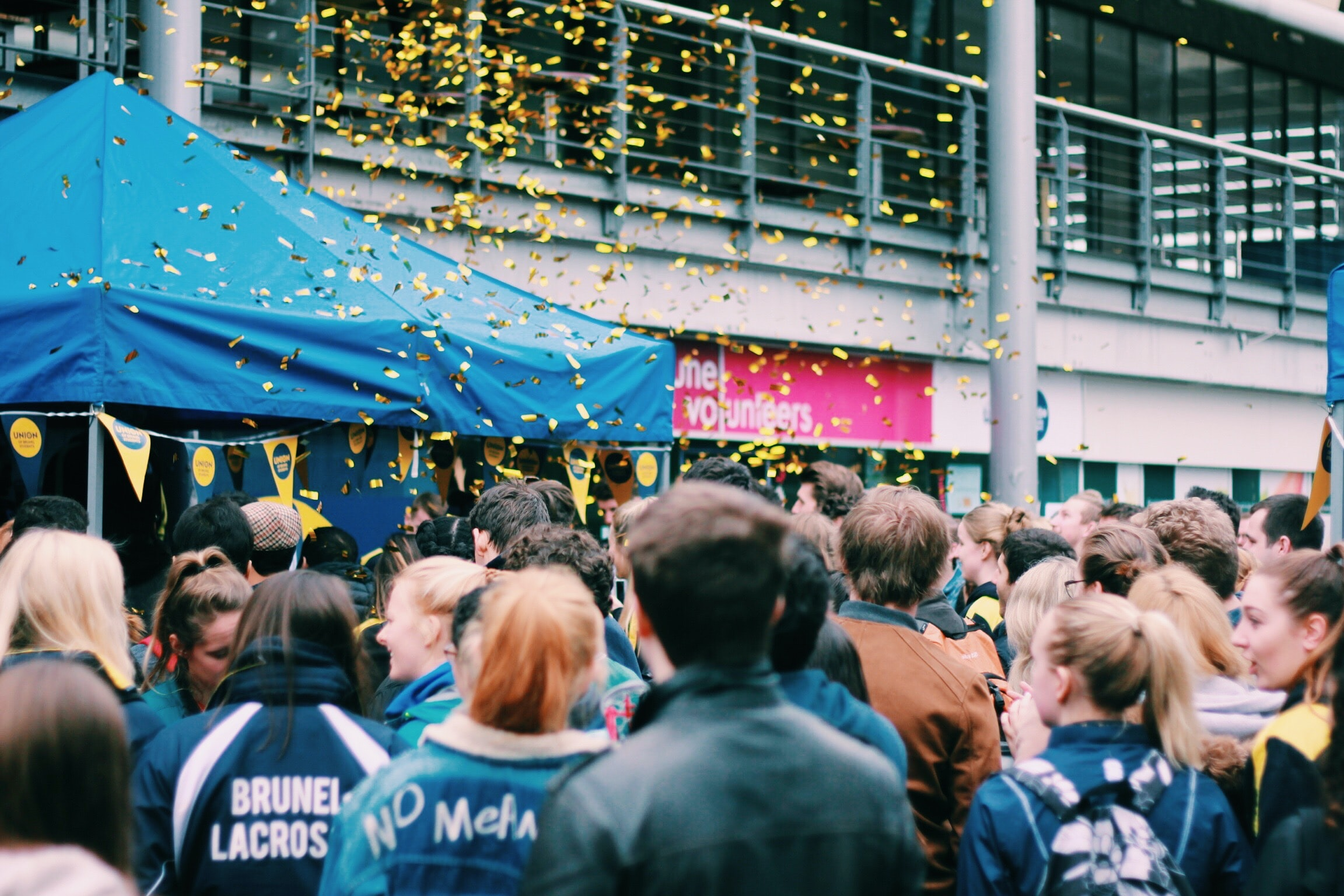 people celebrating outside building with flying confettis