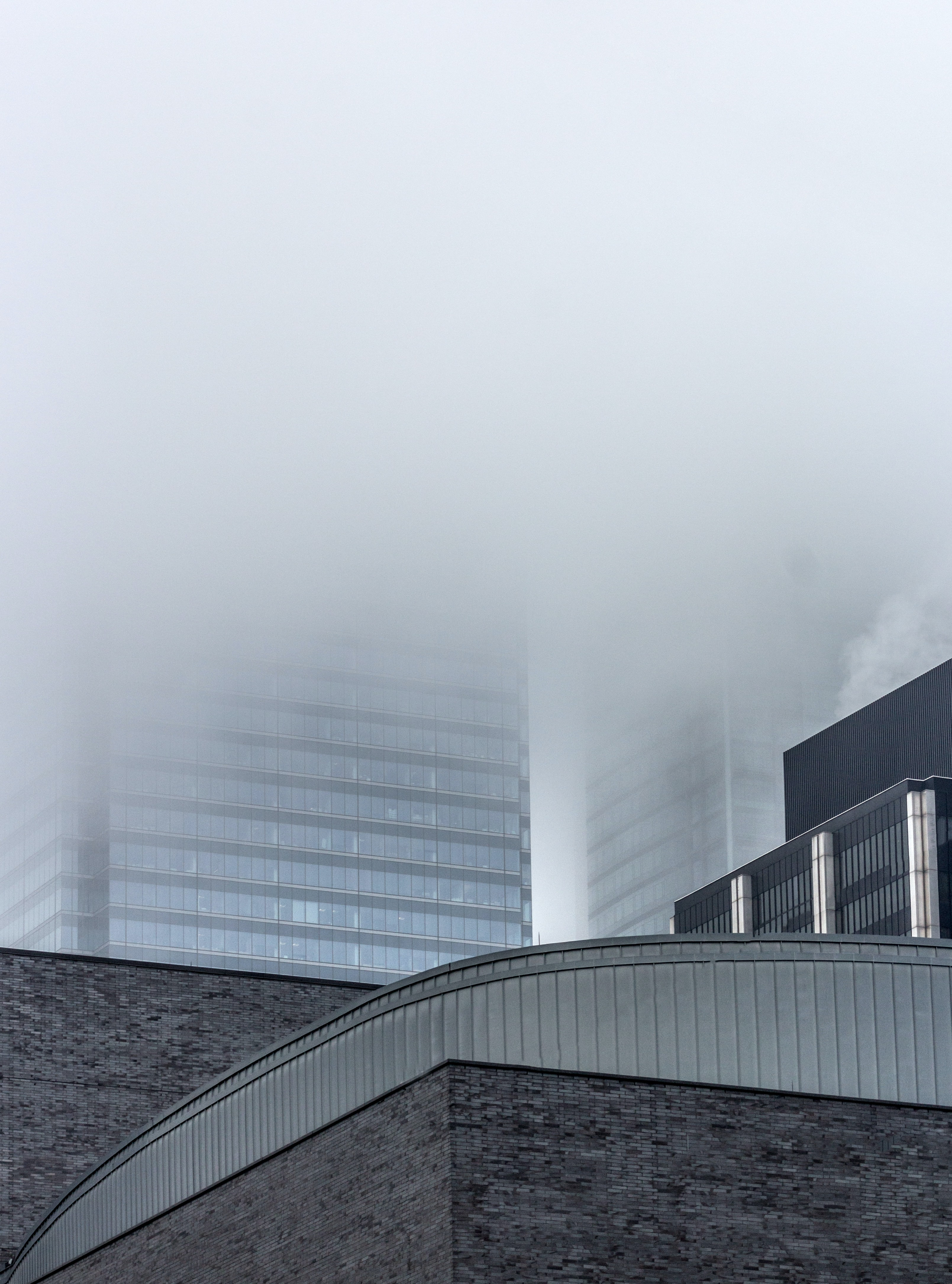 low-angle photography of building surrounded by clouds