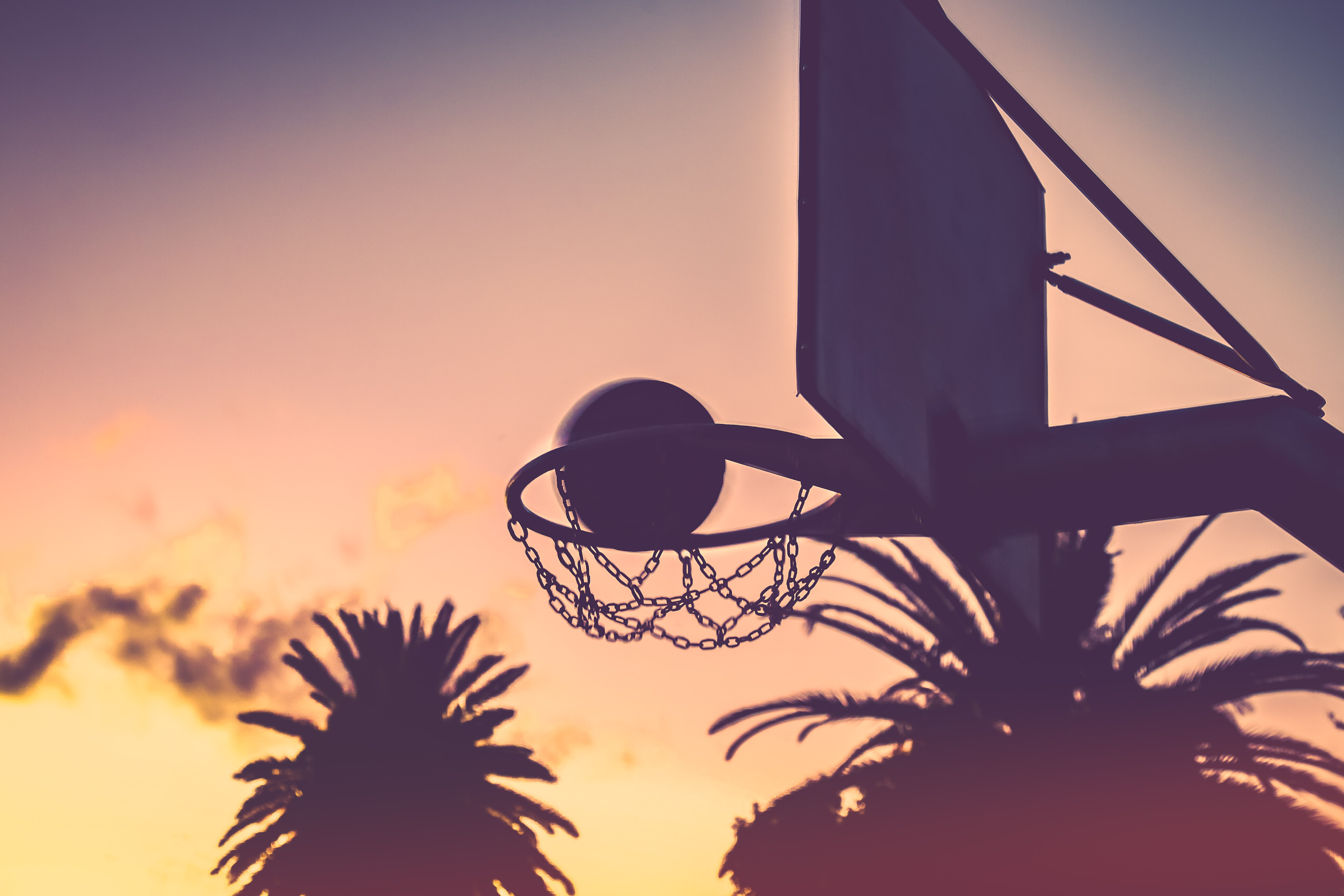 silhouette of basketball hoop and basketball during orange sunet