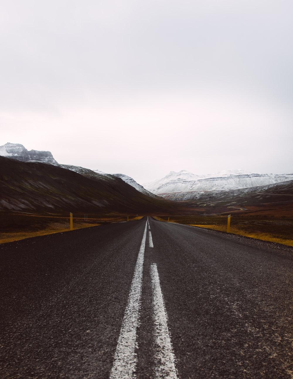 gray asphalt road under cloudy sky