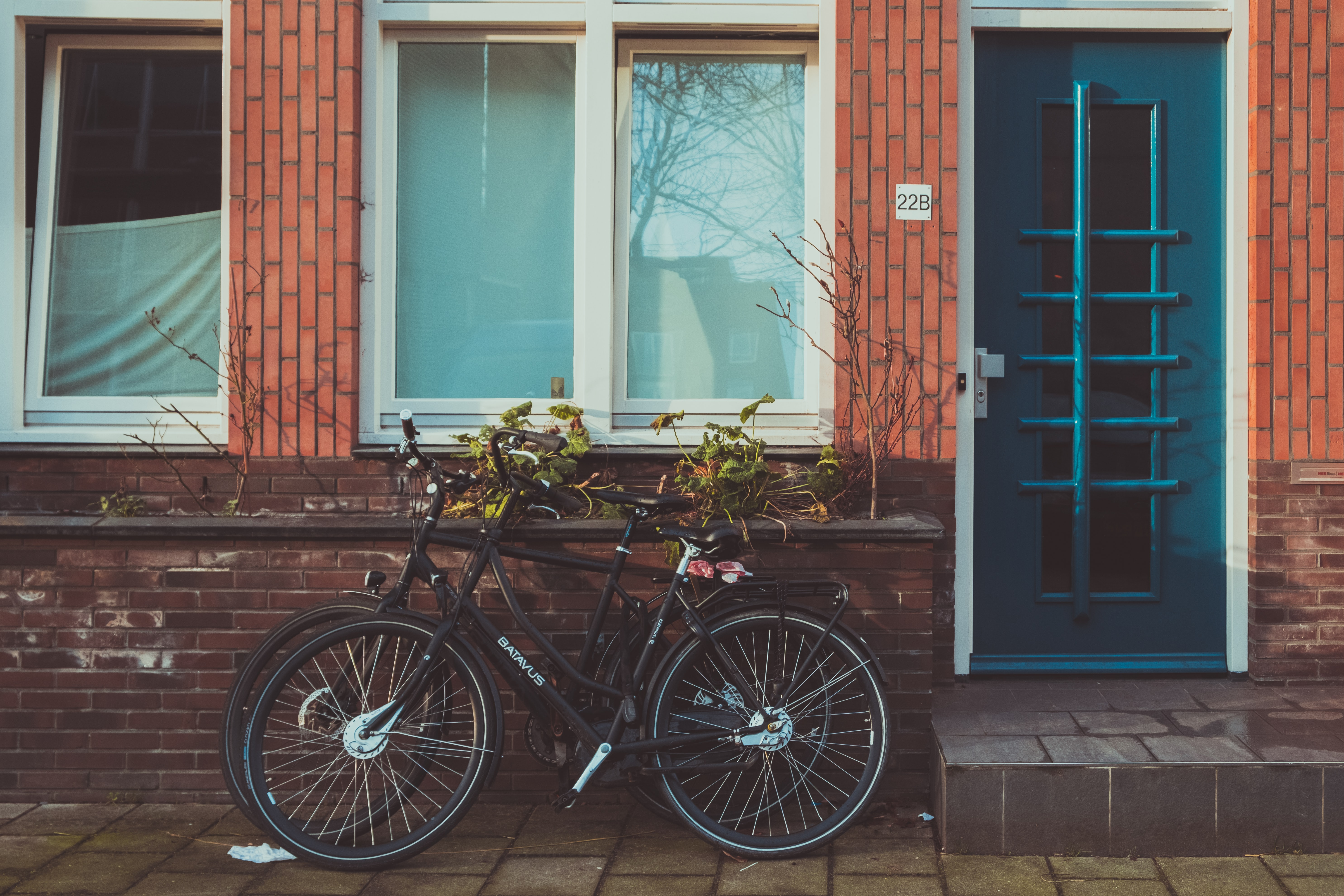 black road bicycles beside brown concrete wall during daytime