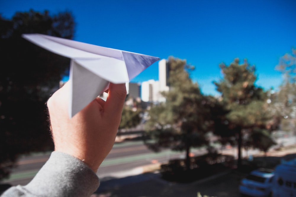 person holding paper plane